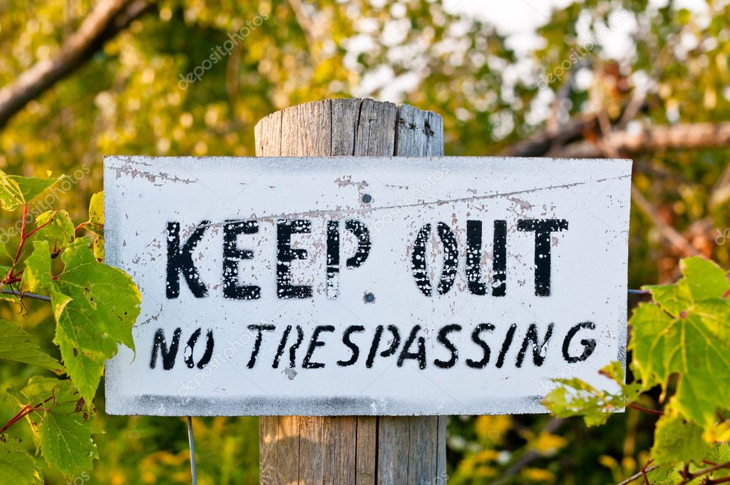 An old weathered sign reading Keep out - No trespassing is nailed to a wooden fencepost. — Stock Photo #4082958
