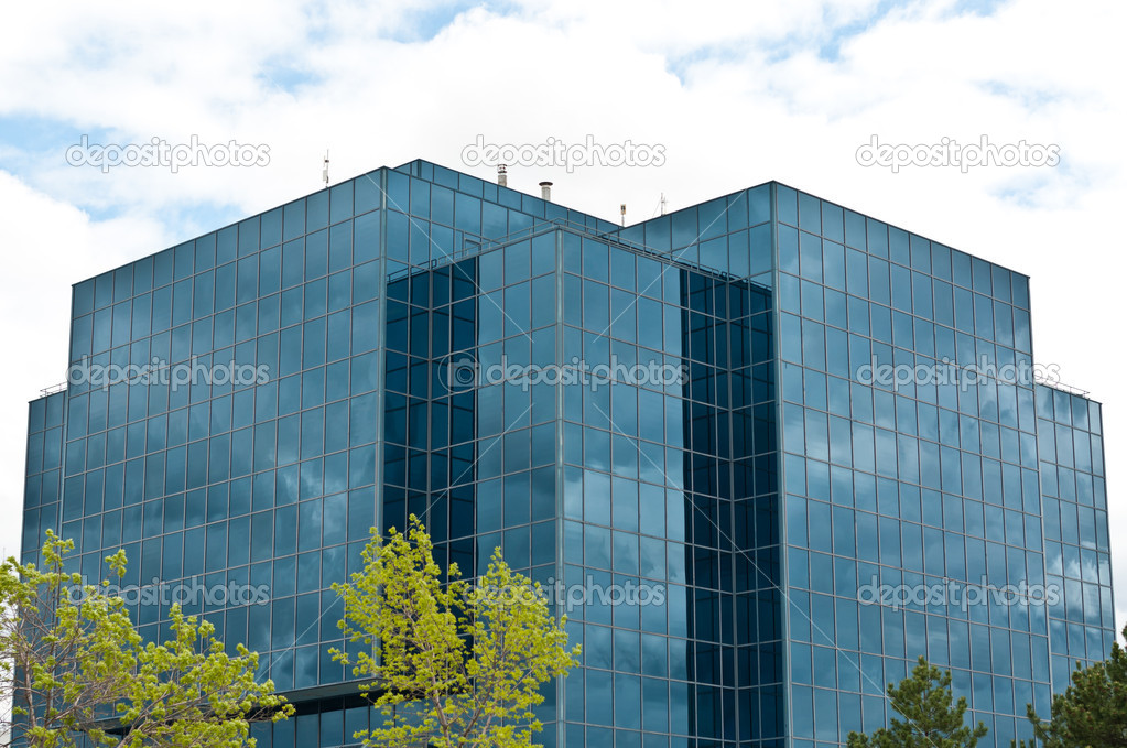 A modern office building reflecting the clouds and surrounded by trees. — Stock Photo #4092453
