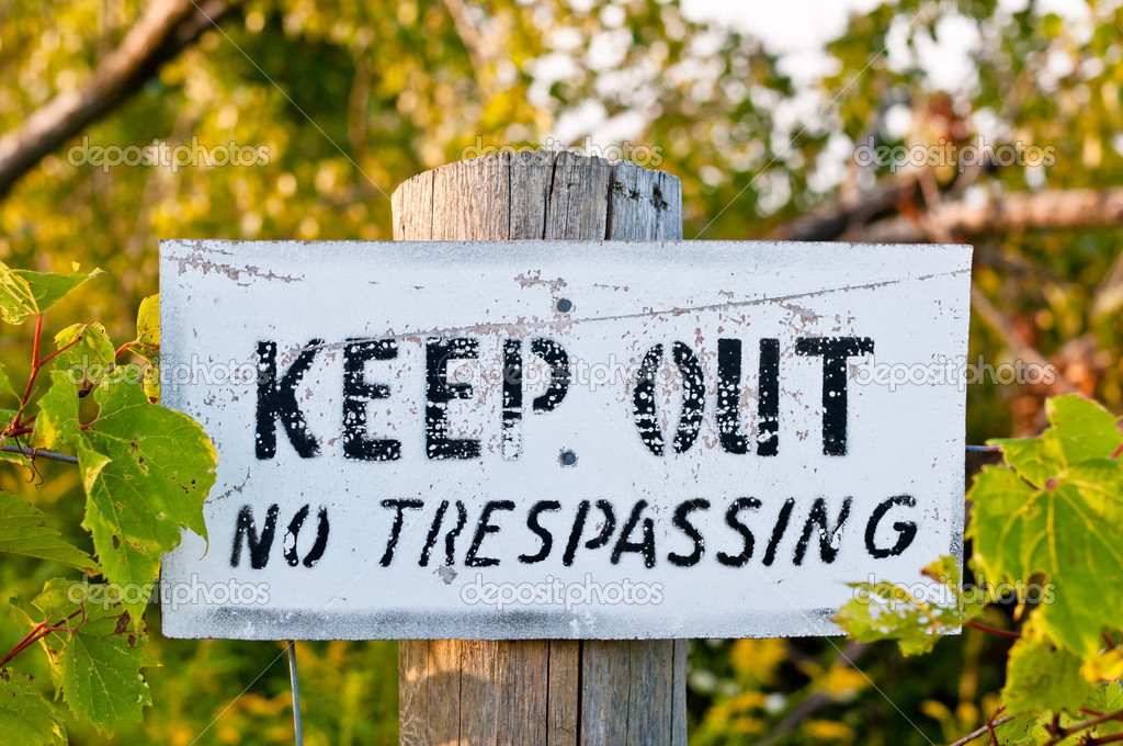 An old weathered sign reading Keep out - No trespassing is nailed to a wooden fencepost. — Stock Photo #4131434