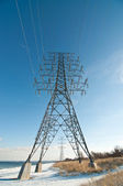 Electrical Transmission Tower (Electricity Pylon) beside a lake — Stock Photo