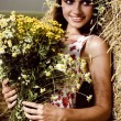 Beautiful woman with flowers near a haystack — Stock Photo