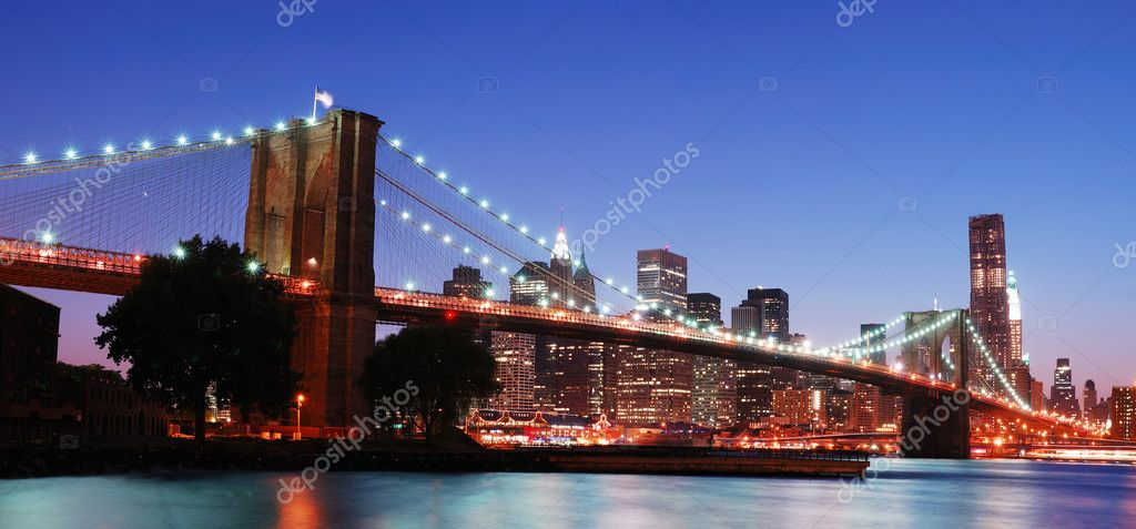 New York City Brooklyn Bridge and Manhattan skyline panorama view with skyscrapers over Hudson River illuminated with lights at dusk after sunset. — Stock Photo #4001729