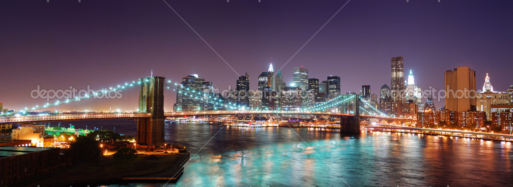 New York City Brooklyn Bridge and Manhattan skyline panorama view with skyscrapers over Hudson River illuminated with lights at dusk after sunset.  Stock Photo #4001734