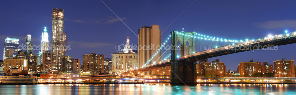 New York City Manhattan skyline panorama with Brooklyn Bridge and office skyscrapers building in at dusk illuminated with lights at night  Stockfoto #4001751