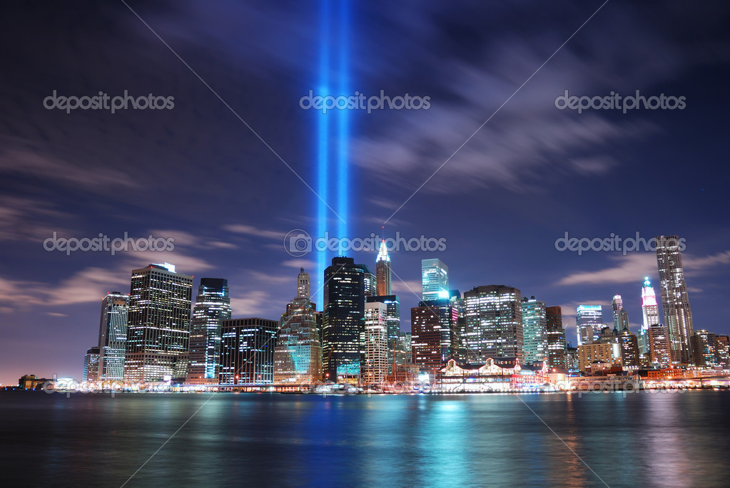 Remember September 11. New York City Manhattan panorama view at night with office building skyscrapers skyline illuminated over Hudson River and two light beam  — Stock Photo #4025715