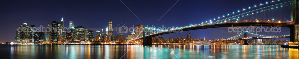 New York City Manhattan skyline panorama with Brooklyn Bridge and office skyscrapers building in at dusk illuminated with lights at night  Stock Photo #4026089