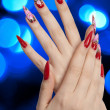 Beautiful red nails and blue lights - Stock Photo