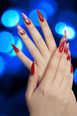 Beautiful red nails and blue lights — Stock Photo