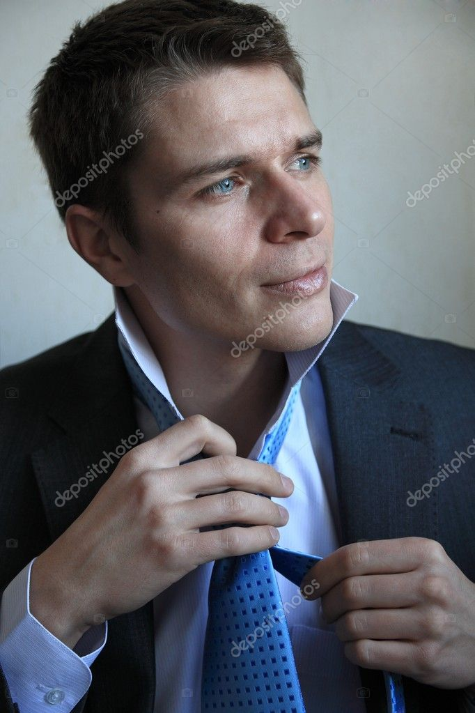 A handsome young businessman tying his tie — Stock Photo #4148118