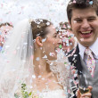Bride and Groom in confetti shower — Stockfoto