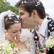 Bride and Groom in confetti shower — Stock Photo