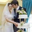 Bride and Groom cutting wedding cake - Stockfoto