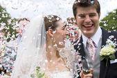 Bruid en bruidegom in confetti douche — Stockfoto