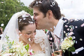 Bride and Groom in confetti shower — Stock Photo