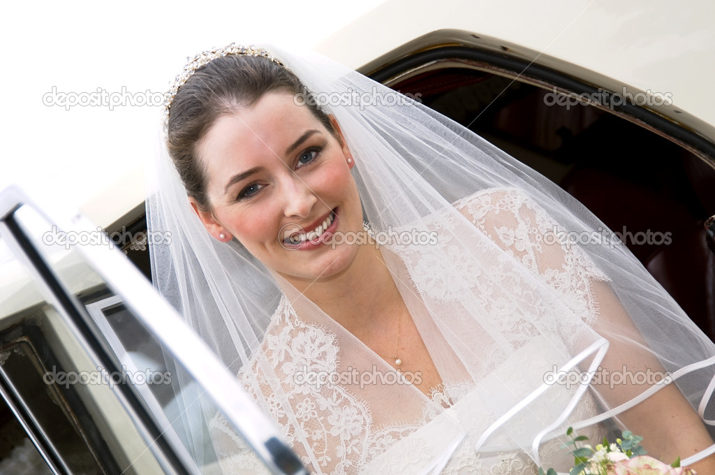 A radient looking bride getting out of wedding car — Stock Photo #4018208