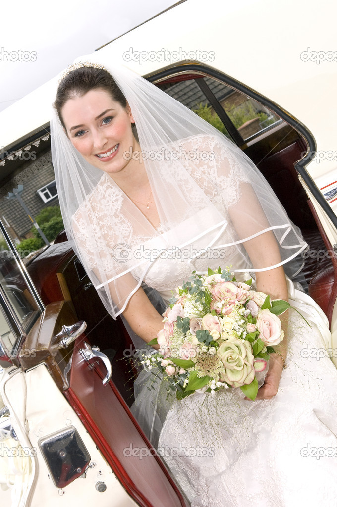 A radient looking bride getting out of wedding car — Stock Photo #4018234