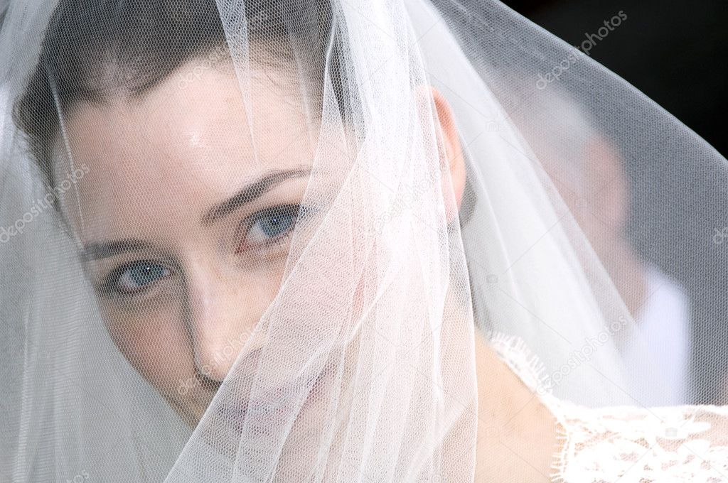 A blue eyed bride looking through hr wedding veil — Stock Photo #4018287