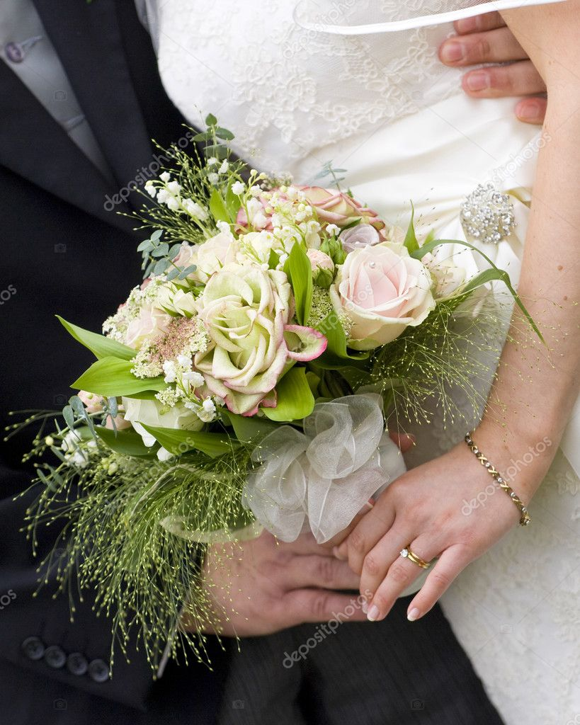 A close up of a beautiful bridal bouquet held by the bride and groom — Stock Photo #4018389