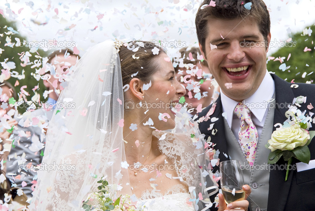 A really happy looking bride and groom being showered with confetti by htier guests — Lizenzfreies Foto #4018555