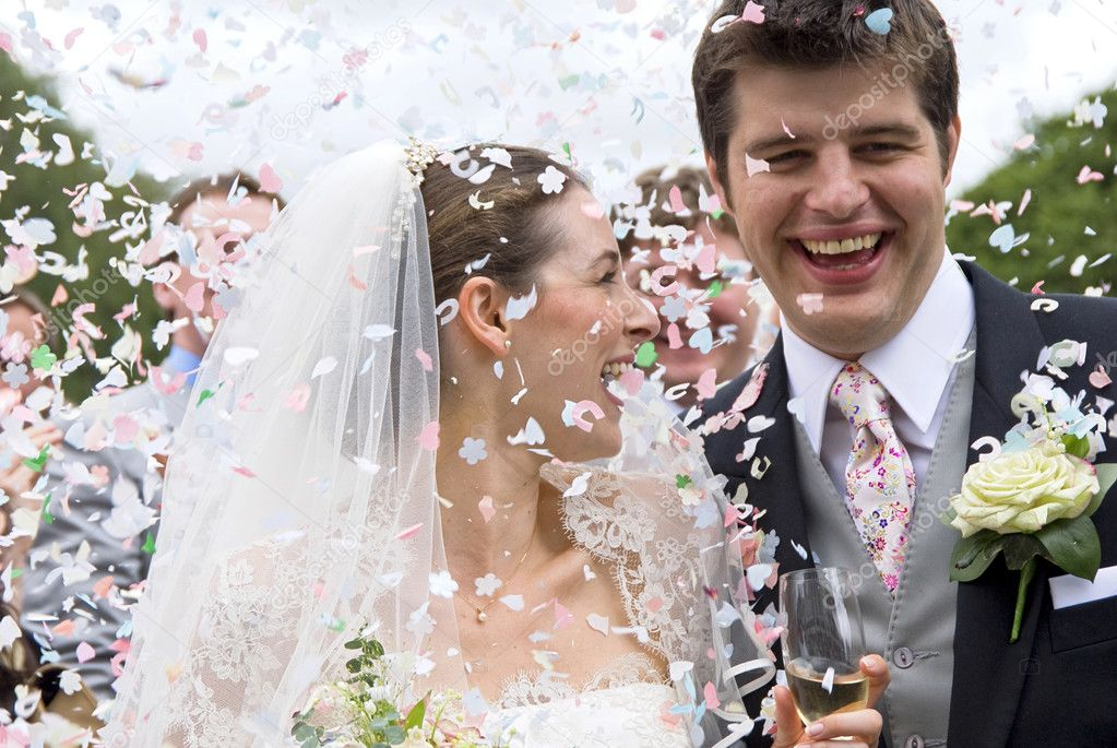 A really happy looking bride and groom being showered with confetti by htier guests — Zdjęcie stockowe #4018555