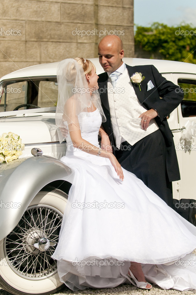 A stunning looking bride and groom next to a vintage wedding car — Zdjęcie stockowe #4018765