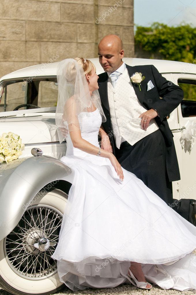 A stunning looking bride and groom next to a vintage wedding car — Stok fotoğraf #4018765