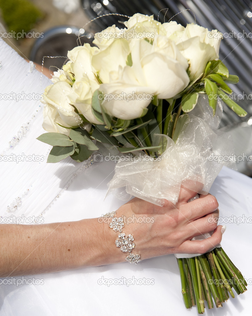 Close up of a  bride holding a beautiful bouqet of cream roses with a vintage wedding car in the background — Stock Photo #4018864
