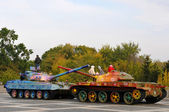 Military tank painted in colorful flowers — Stock Photo