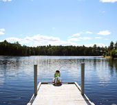 Child on dock at lake — Stock Photo