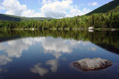 Scenic mountain pond with reflection of sky — Stock Photo