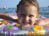 Happy baby on an inflatable disc in a sea of close-ups. — Stock Photo