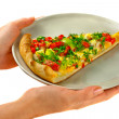 Woman's hands holding a pizza on a plate. — Stock Photo #4107453
