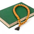 A book with a green cover and wooden rosary. — Stock Photo