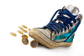 Gold coin rolled under the sneakers. — Stock Photo