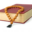 Old book with a claret  cover and wooden rosary. — Stock Photo