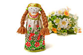 Russian traditional doll in dress and a bouquet of flowers. — Stock Photo