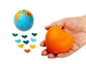 Orange heart in hand over the globe and small hearts for valent — Stock Photo