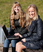 Zwei mädchen mit einem laptop lächelnd — Stockfoto