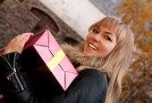 Bir hediye ile genç gülümseyen kız — Stok fotoğraf