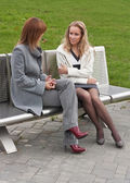 Two girls talking on a bench — Stock Photo