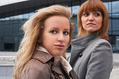 Two pretty girls near business building — Stock Photo