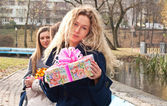 Beautiful young blond girl with a present — Стоковое фото