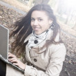 Royalty-Free Stock Photo: Smiling young brunette girl with a laptop in the park
