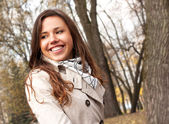 Cute smiling young brunette girl in the park — Stock Photo