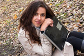 Pretty brunette girl with a laptop in the park — Stock Photo
