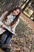 Güzel genç kız parkta bir laptop holding — Stok fotoğraf