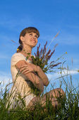 Woman with flowers on green meadow — Stock Photo