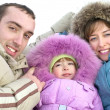 Royalty-Free Stock Photo: Happy young parents with daughter on to snow