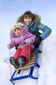 Mother and little daughter sliding in the snow — Stock Photo