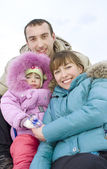 Happy young family spending time outdoor in winter — Stock Photo
